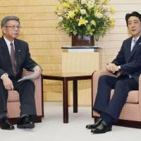Prime Minister Shinzo Abe and Okinawa Gov. Takeshi Onaga talk in Tokyo on Friday. | KYODO