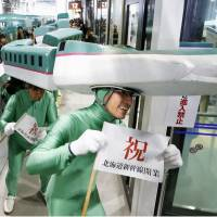 Men in train costumes welcome the arrival of a train from Tokyo in Hakodate. | KYODO