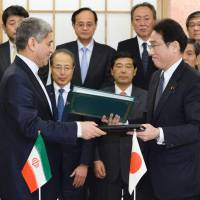 Iranian Minister of Economic Affairs and Finance Ali Taiebnia (left) and Foreign Minister Fumio Kishida sign a bilateral investment pact in Tokyo on Feb. 5. | POOL / KYODO