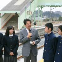 Prime Minister Shinzo Abe speaks with local high school students at JR Odaka Station on the Joban Line in Minamisoma, Fukushima Prefecture, on Saturday during a visit to the area. | POOL