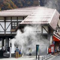 A hot spring spews steam in front of Unazuki Onsen Station in Kurobe, Toyama Prefecture, on Nov. 16. The station is a mountain terminus of the Toyama Chiho Railway. | KYODO