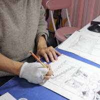 Kazuto Tatsuta, who has been involved in decommissioning work at the Fukushima No. 1 nuclear plant, works on a new manga story at his office in a Tokyo suburb on Feb. 16. | KYODO