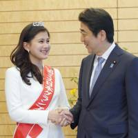 Mika Matsuno, winner of the 2016 Miss Nippon beauty pageant, shakes hands with Prime Minister Shinzo Abe at his office in Tokyo Friday. Matsuno, a 20-year-old sophomore at Keio University, is the daughter of Yorihisa Matsuno, who leads opposition party Ishin no To (Japan Innovation Party). | KYODO