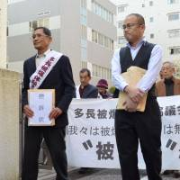 Takeshi Yamauchi (left), leader of a group of 151 plaintiffs seeking to be acknowledged as hibakusha, heads to the Nagasaki District Court on Monday. | KYODO