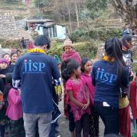 Nepalese teens distribute winter items for young disaster survivors in Nepal in January. The project was supported by disaster-hit teens in Japan. | COURTESY OF JAPAN ISRAAID SUPPORT PROGRAM / KYODO