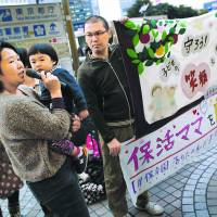 Makiko and Kazuhiko Morohoshi, with their 2-year-old son Amane, attend a rally in Tokyo on March 20 protesting a lack of day care centers in Japan.  | REUTERS