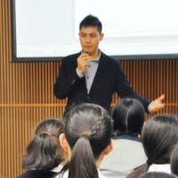 Students at Seishin Joshi Gakuin school in Tokyo listen to a speech in December by Jafar Atayee, an Afghan who came to Japan in 2009 after fleeing his home country and who has since sought refugee status. | KYODO