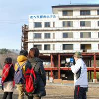 Students listen as a tour guide explains the magnitude of the March 2011 quake and tsunami in front of the former Taro Kanko Hotel in Miyako, Iwate Prefecture, in late February.   KYODO
