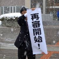 A banner is held up in front of the Sapporo District Court on Thursday hailing the reopening of a case involving a 46-year-old Russian who received a two-year prison term for possessing a gun in 1997. | KYODO