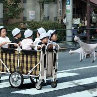 An artist's rendering shows a sentinel drone guiding a cart of nursery school children. Officials say the drones, part of the ambitious Roho Care project, will be ready for a trial run as early as summer 2016. | PJAN VANDAELE / THE JAPAN TIMES
