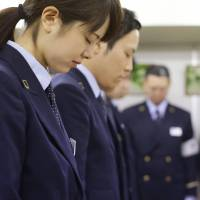 Tokyo Metro Co. workers hold a moment of silence Sunday in honor of the victims of the 1995 sarin nerve gas attack at Kasumigaseki Station in Tokyo's Chiyoda Ward. | KYODO