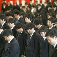 Graduating students of Takata High School in Rikuzentakata, Iwate Prefecture, offer prayers to the March 2011 victims during a graduation ceremony on Tuesday. | KYODO