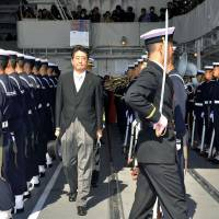 Prime Minister Shinzo Abe receives a salute on the Maritime Self-Defense Force destroyer Kurama docked at Sagami Bay in Kanagawa Prefecture in October. | Kyodo