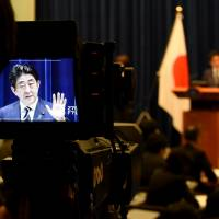 A cameraman focuses on Prime Minister Shinzo Abe during a news conference on Tuesday, when two divisive security laws punctured Japan's pacifist postwar defense profile. | AFP-JIJI