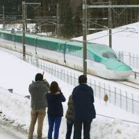 People photograph a trial run of the Hokkaido Shinkansen Line on Jan. 1, 2016, in Kikonai, Hokkaido. Trains start operations Saturday, 43 years after the plan to build the line was first adopted by the government. | KYODO