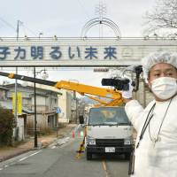 Yuji Onuma looks on as workers on Dec. 21 begin removing a sign bearing a slogan he wrote, in the town of Futaba, Fukushima Prefecture, that reads 'Nuclear power: the energy for a bright future.' | KYODO