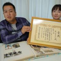 Yuji Onuma and his wife, Serina, display a certificate received for the winning slogan, on Feb. 9. | KYODO