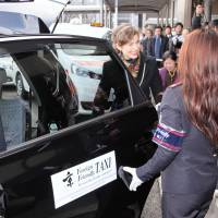 A tourist gets into a 'foreigner-friendly taxi' in Kyoto on Tuesday. The service is aimed at enhancing the experience of overseas visitors to the ancient capital. | KYODO