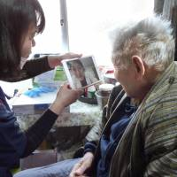 Patient Akira Fujisawa talks with his doctor via video link using a tablet computer at his home in Takamatsu, Kagawa Prefecture, on March 1. | KYODO