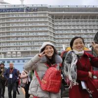 Chinese tourists arrive at Fukuoka port on a cruise passenger ship last month. A Chinese tourist was found to have been illegally working as a tour guide in the city. | KYODO