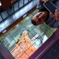 A man takes a photo with his smartphone from the observation deck of Tokyo Tower in Minato Ward last Thursday. | SATOKO KAWASAKI
