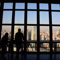 Tourists take in the view from the observation deck of Tokyo Tower last Thursday. | SATOKO KAWASAKI