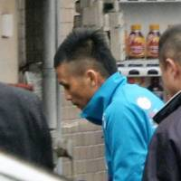 Narimichi Minami, who was arrested Friday for allegedly causing a deadly pileup inside a tunnel in Hiroshima Prefecture the previous day, enters a police station in Hiroshima Friday. | KYODO
