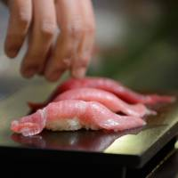 Tuna sushi is served at a restaurant in Tokyo. Firms are increasingly looking to bluefin tuna farming as the fish population in the sea declines. | BLOOMBERG