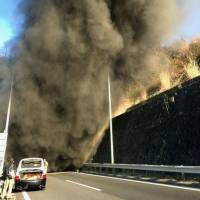 A photo posted to Twitter shows black smoke coming out of the Hachihonmatsu tunnel on the Sanyo Expressway in Higashihiroshima, Hiroshima Prefecture, on Thursday. | KYODO