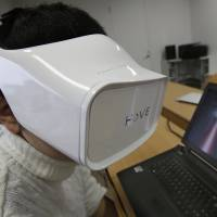 A Fove worker demonstrates an eye-tracking headset at the company's office in Tokyo on March 7. | AP