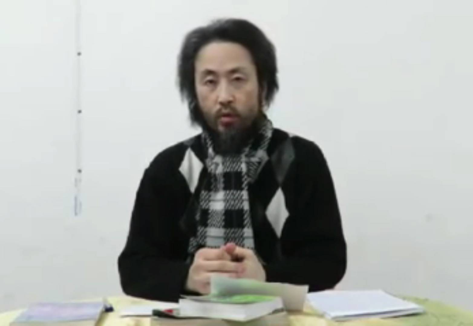 A man who appears to be Jumpei Yasuda, a journalist who went missing in Syria last year, is seen speaking in this screen shot of a video uploaded to Facebook on Thursday. | FACEBOOK