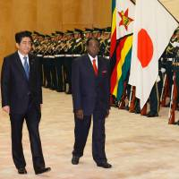Zimbabwe President Robert Mugabe walks with Prime Minister Shinzo Abe as they review an honor guard before their meeting at Abe's office Monday. | AFP-JIJI