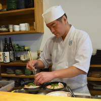 Seafood stack: Chef Futoshi Fujimoto puts the final touches on his version of the kaisendon, a generous serving of fresh sashimi on a bed of rice. | J.J. O'DONOGHUE