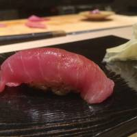Sato's signature series of different cuts of tuna comprises <em>akami</em>, which has been briefly marinated in soy sauce; followed by the lighter-colored, creamier <em>chū-toro</em> (above); and finally the richly marbled, fatty <em>ōtoro</em> meat.  | ROBBIE SWINNERTON