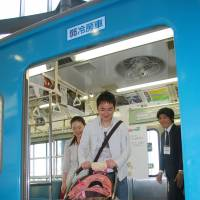 A man pushes a stroller off a train at Saitama Railway Museum. | KYODO