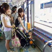 A woman uses a space devoted to strollers on a tram operated by Hiroshima Electric Railway. | KYODO