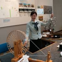 A staffer at the Toyota Commemorative Museum of Industry and Technology demonstrates cotton spinning. | MARK ANDREWS