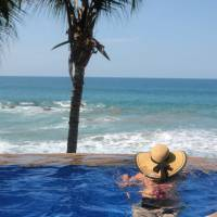 A woman gazes over the Pacific Ocean from a swimming pool at Playa Escondida hotel in Sayulita, Mexico | AP
