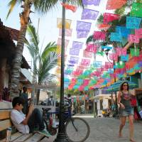 Living color: A woman walks down a street in Sayulita, Mexico. | AP