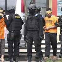 A closer fight: Indonesian police lead away two men who are suspected of involvement in January's militant attack in Jakarta. The attack has exposed terrorist elements closer to Japan's shores. | REUTERS