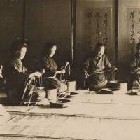 A historical photograph of women at Nakagawa Masashichi Shoten carrying out oumi — the process of splitting hemp yarn and joining it into a long continuous thread.