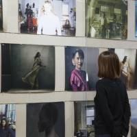 A visitor looks at images of Annie Leibovitz' 'Women: New Portraits' exhibition at Tolot / Heuristic Shinonome in Tokyo. | KIOKU KEIZO