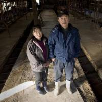 Kenichi Hasegawa and his wife visit his now-vacant dairy farm in Iitate village in December 2011. | TAKASHI MORIZUMI