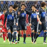 Japan's Mu Kanazaki (15) is congratulated by teammates after scoring a 78th-minute goal against Afghanistan on Thursday. | AFP-JIJI