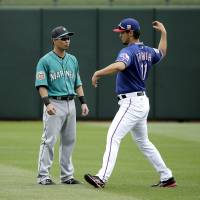 The Mariners' Norichika Aoki (left) speaks with Rangers pitcher Yu Darvish before a spring training game on Sunday in Surprise, Arizona. | AP