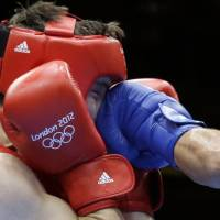 Britain's Freddie Evans is hit with a punch from Kazakhstan's Serik Sapiyev during their welterweight 69-kg gold-medal match at the 2012 London Olympics. | AP
