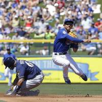 Chicago's Munenori Kawasaki throws to first base after forcing out Milwaukee's Keon Broxton during a March 25 preseason game. | AP