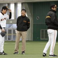 Yomiuri Giants pitcher Kyosuke Takagi (far left) shares a joke with manager Yoshinobu Takahashi (far right) during a February training camp in Miyazaki. | KYODO