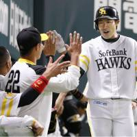 The Hawks' Yuki Yanagita (right) fired up his teammates on Friday, when he slugged two home runs in a game against the Tigers that ended in a 3-3 tie in Fukuoka. | KYODO