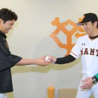 Giants starter Tomoyuki Sugano (left) presents a game ball to Yoshinobu Takahashi, who earned a victory in his managerial debut on Friday. | KYODO